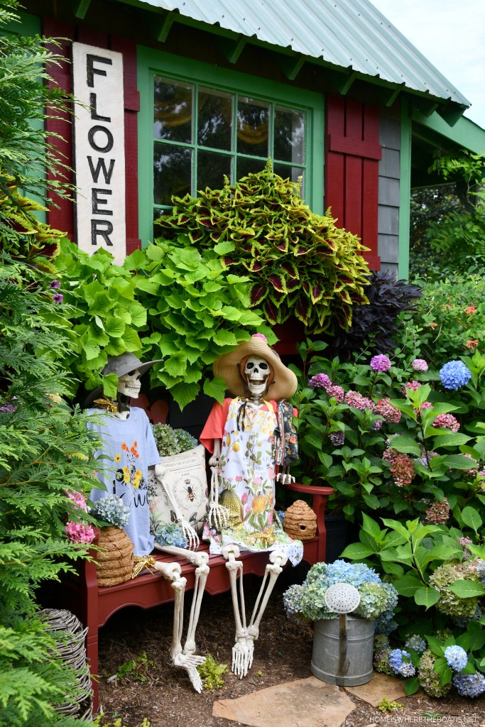 Rod and Rowena rest their weary bones and take a break from gardening | ©homeiswheretheboatis.net #skeleton #halloween #garden #flowers #bees