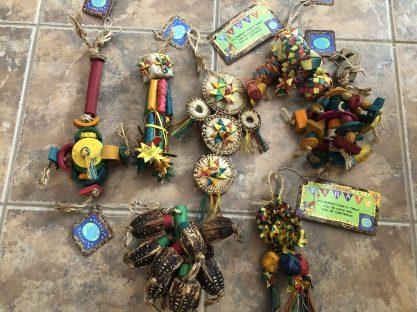 Several new parakeet toys on a tile floor