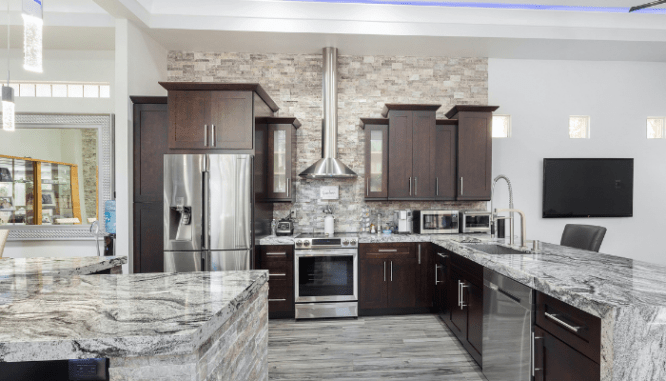 A grey kitchen with granite countertops.