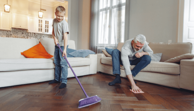 A father cleaning a house with his son before hiring a real estate agent.