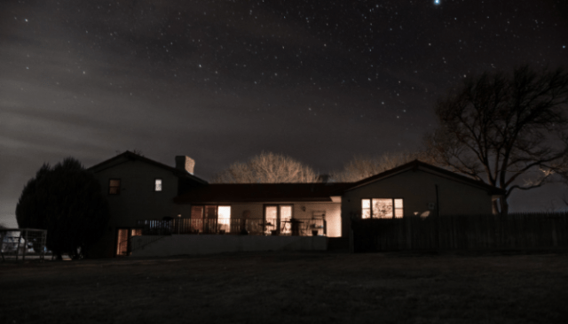 An image of a house at night used to show the importance of crime reports in your neighborhood.