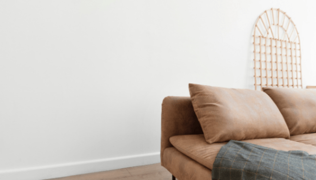 An image of a couch and pillows to demonstrate the process of furnishing a new home.