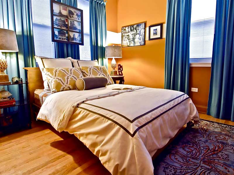 Orange Bedroom With Bold Blue Curtains