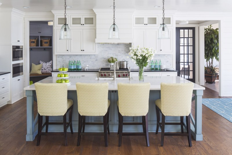 White kitchen with cream leather bar stools. Kitchen with glass pendant lights over blue kitchen island with white countertop