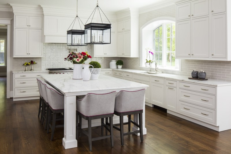 White kitchen with gray tiled backsplash with dark wood floors. Kitchen with lantern pendant lights over white kitchen island with white countertop