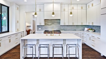 White kitchen with marble tile backsplash and glass bar stools. Kitchen with mini gold pendant lights over white kitchen island with laminate countertops