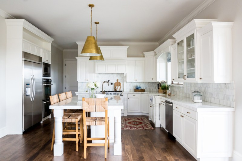 White kitchen with wooden bar stools and dark wood floors. Kitchen with gold pendant lights over kitchen island with white laminate countertop