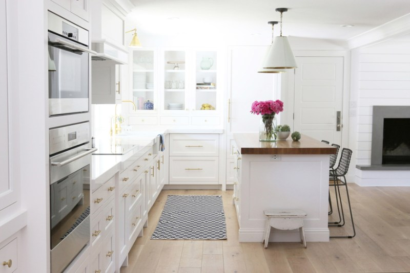 White kitchen with light oak wood flooring. Kitchen with white dome pendant lights over kitchen island with wooden countertops