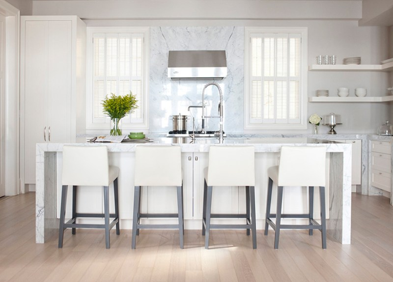 White kitchen with open shelves and marble backsplash. Kitchen with white bar stools and white kitchen island with marble countertops