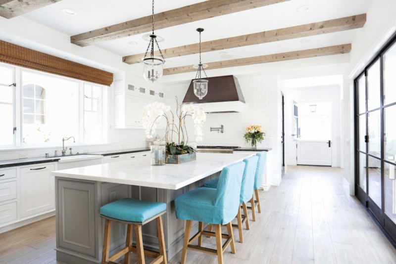 White kitchen with turquoise bar stools. Kitchen with glass pendant lights over gray kitchen island with white laminate countertops