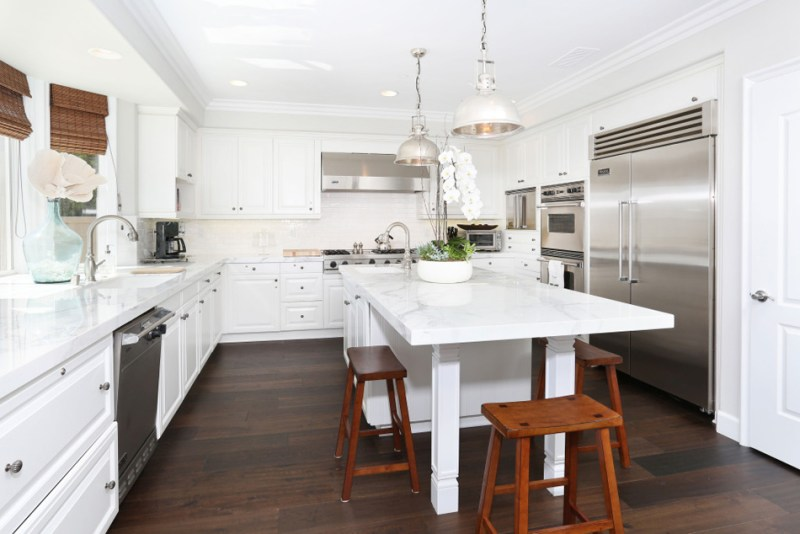 White kitchen with dark hardwood flooring and rustic wooden bar stools. Kitchen with white dome pendant lights over kitchen island with marble countertops