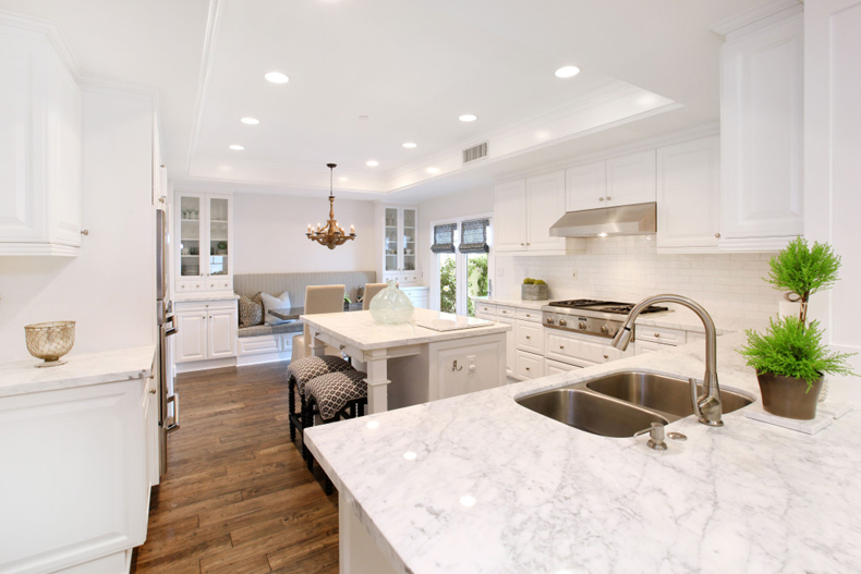 White kitchen with antique wooden chandelier. Kitchen with small kitchen island and black bar stools