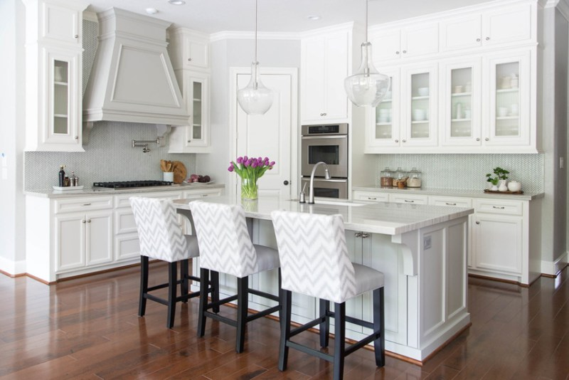 White kitchen black and white bar stools and hardwood floors. Kitchen with glass pendant lights over white kitchen island with marble countertops