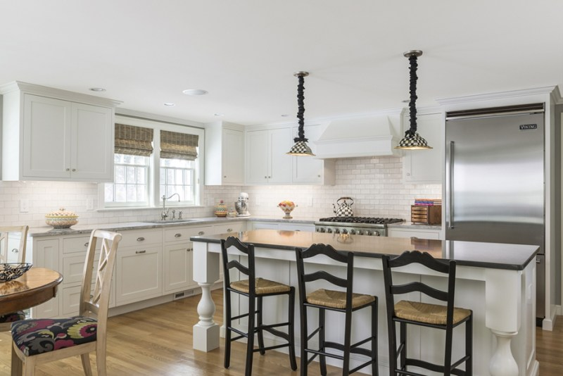 White kitchen with solid wood bar stools. Kitchen with black and white pendant lights over white kitchen island with wooden countertop