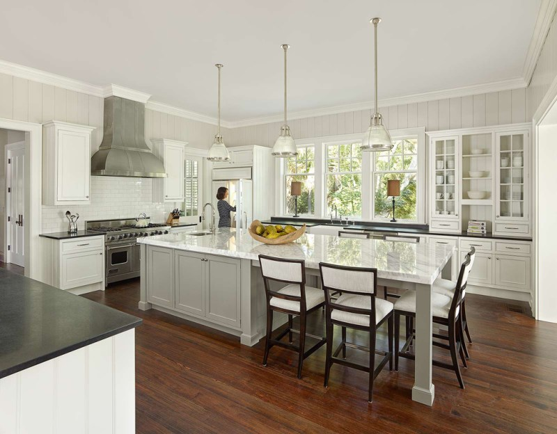 White kitchen with white modern bar stool. Kitchen with white pendant lights over large kitchen island with marble countertop