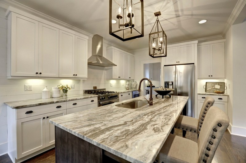 Small white kitchen with cream leather bar stools. Kitchen with iron lantern pendant lights over kitchen island with marble countertop