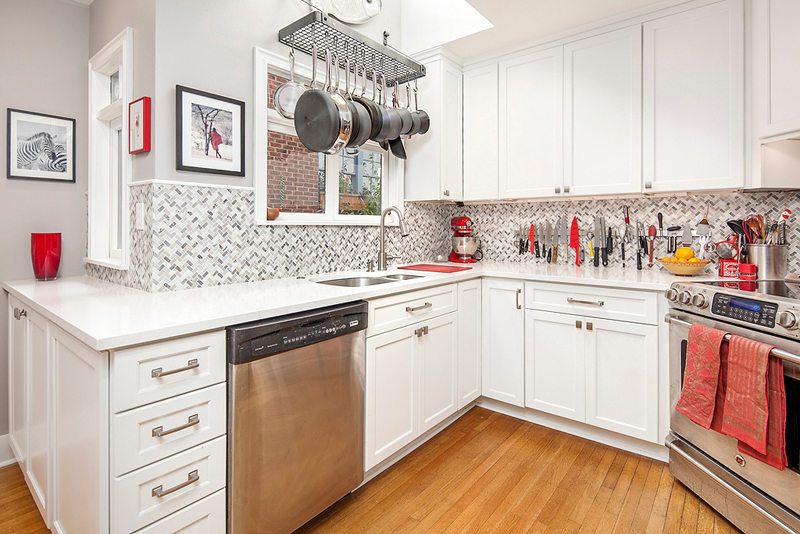 Small white kitchen with light wood flooring and white quartz countertops
