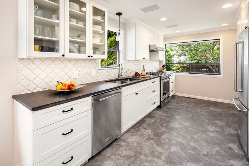 Narrow white kitchen with marble floors. Kitchen with mini pendant lights over countertops with black quartz