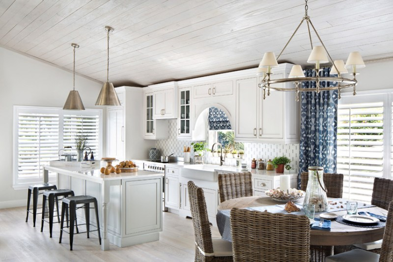 White kitchen with black backless bar stools. Kitchen with brass dome pendant lights over kitchen island with white laminate countertop