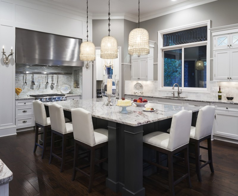White kitchen with white faux leather bar stools. Kitchen with white pendant lights over kitchen island with marble countertop