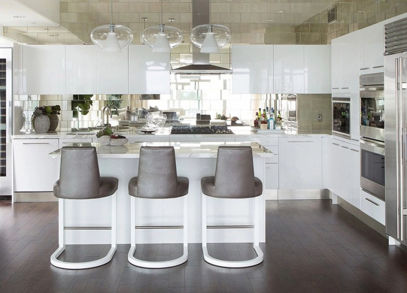 White kitchen with modern gray bar stools. Kitchen with glass pendant lights over kitchen island with marble countertop