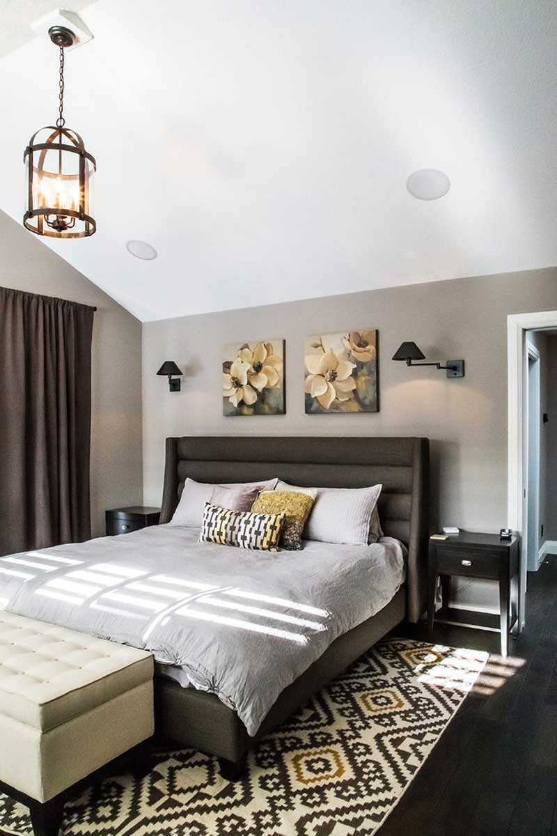 small bedroom with wall sconeces and lantern chandelier foyer