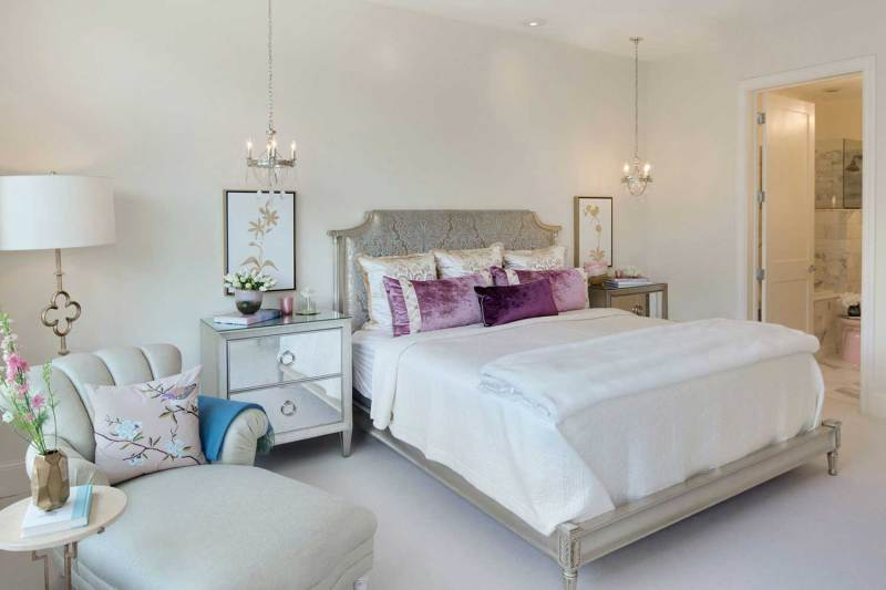 white bedroom with pendant chandeliers
