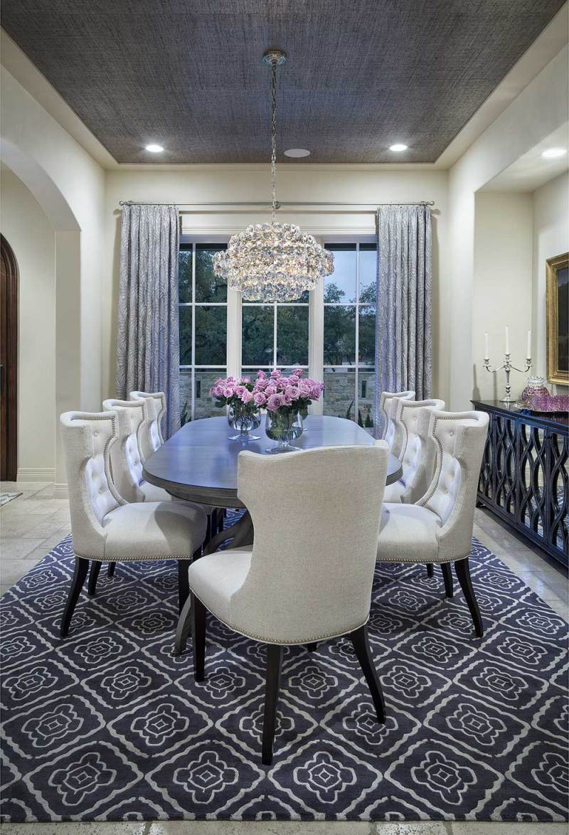 gray and white dining room with crystal chandelier and recessed lighting