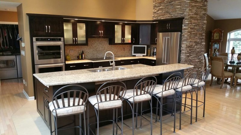 Black kitchen cabinets with white ornamental granite countertops