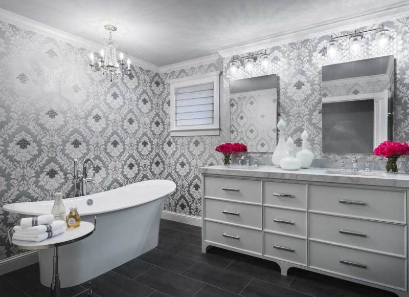 white and gray bathroom with crystal chandelier and wall sconces