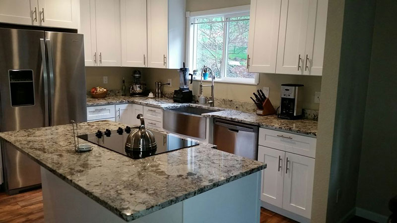 New caledonia granite and white cabinets