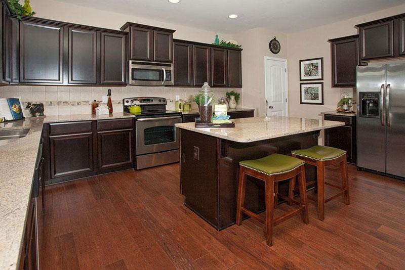 Dark brown cabinets with river white granite
