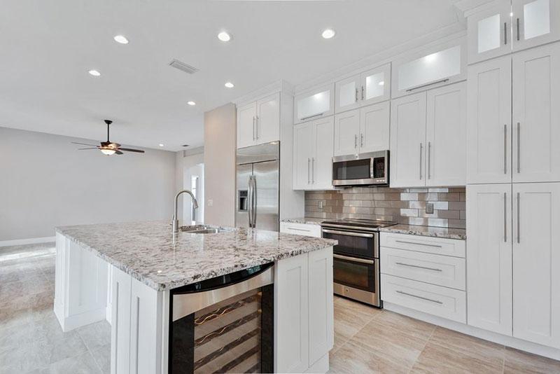 Modern white kitchen design with bianco antico granite countertops