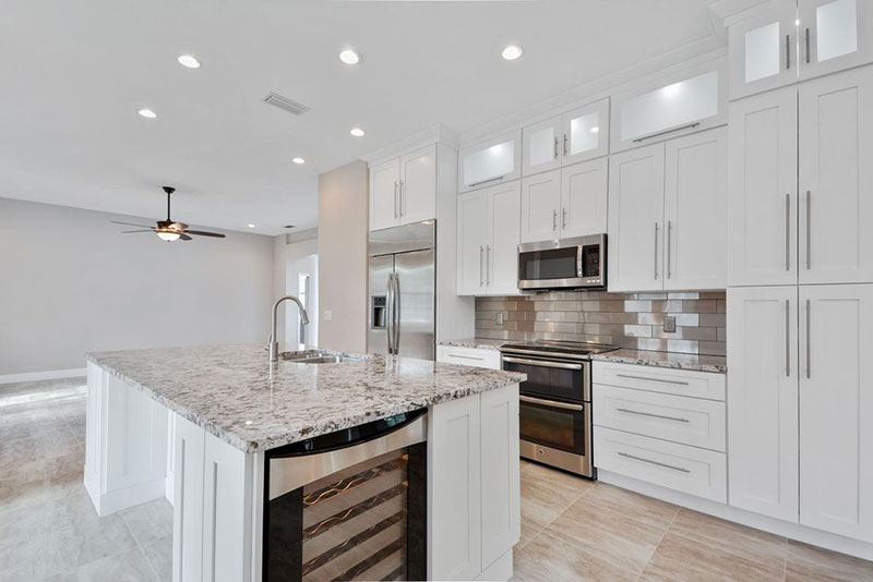 Modern White Kitchen Design With Bianco Antico Granite Countertops