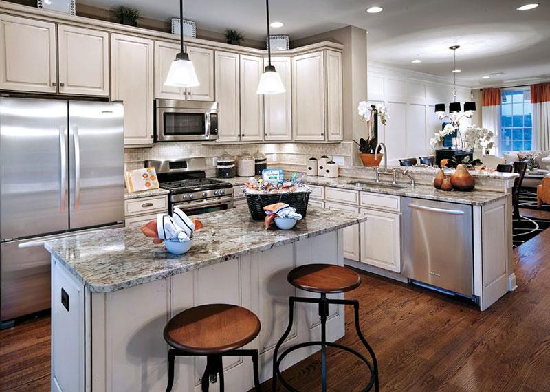 Traditional white kitchen design with bianco antico granite countertops