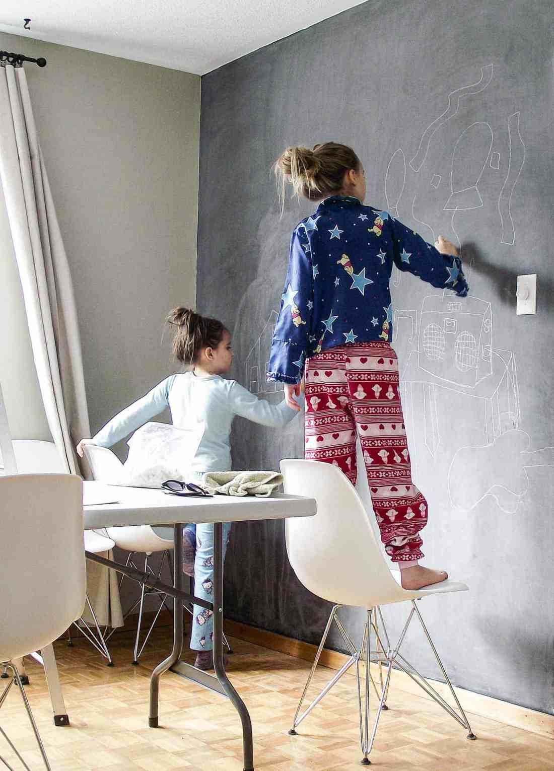 two girls in pajamas wiping chalk off a chalkboard wall