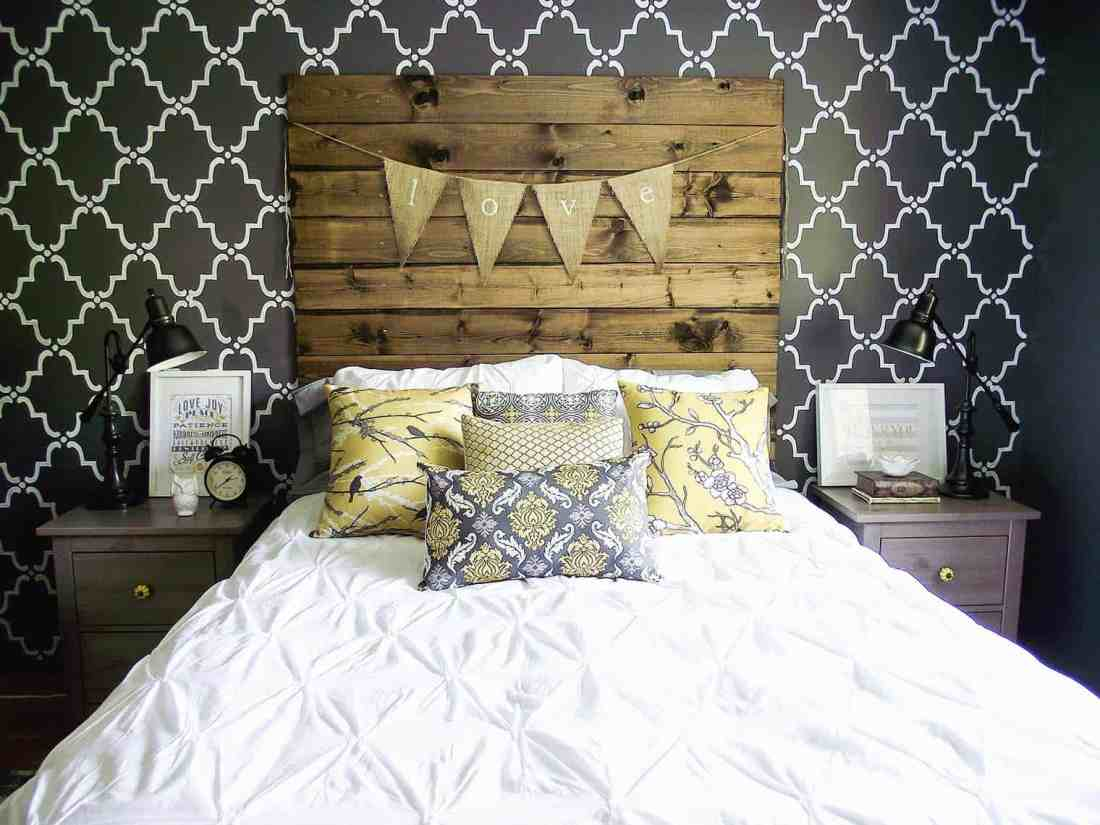 bedroom with wood headboard, stenciled grey and white wall, yellow and grey pillows