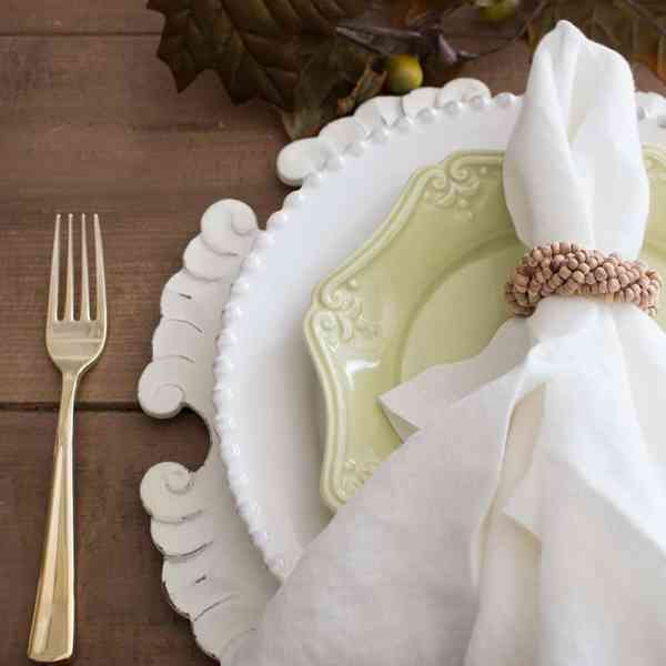 how to make cloth napkins, layered table setting with gold flatware, scalloped charger white and green plates, cloth napkins