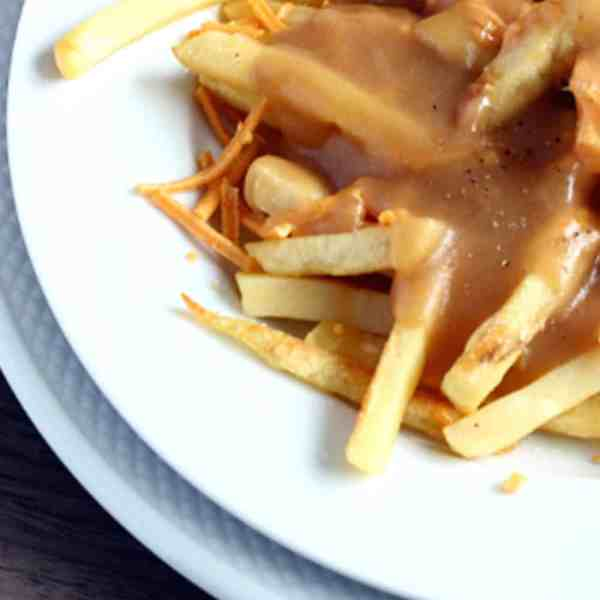 fries, cheese and gravy on a plate, poutine