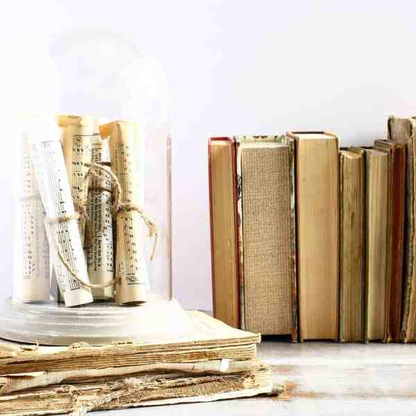 vintage books with a dome cloche, rolled sheet music tied with twine