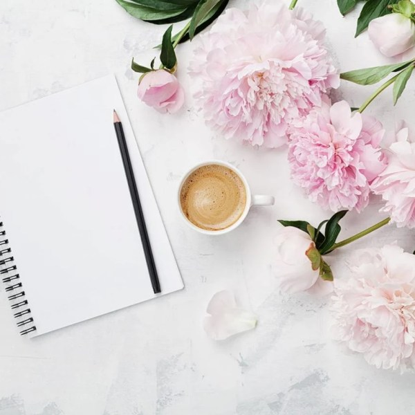 notepad, coffee, flowers on marble counter