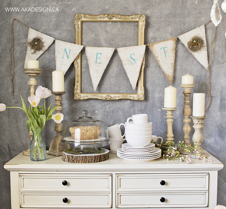 dresser in dining room against chalkboard wall with dishes and spring greenery