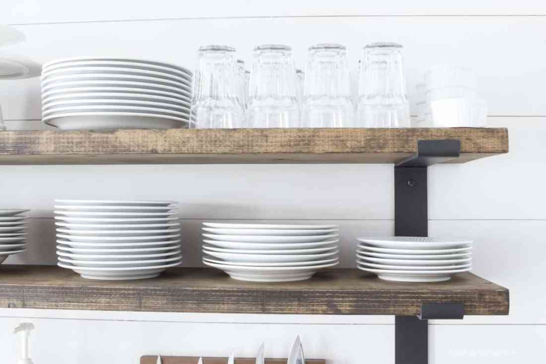 glasses and white dishes on rustic open shelves