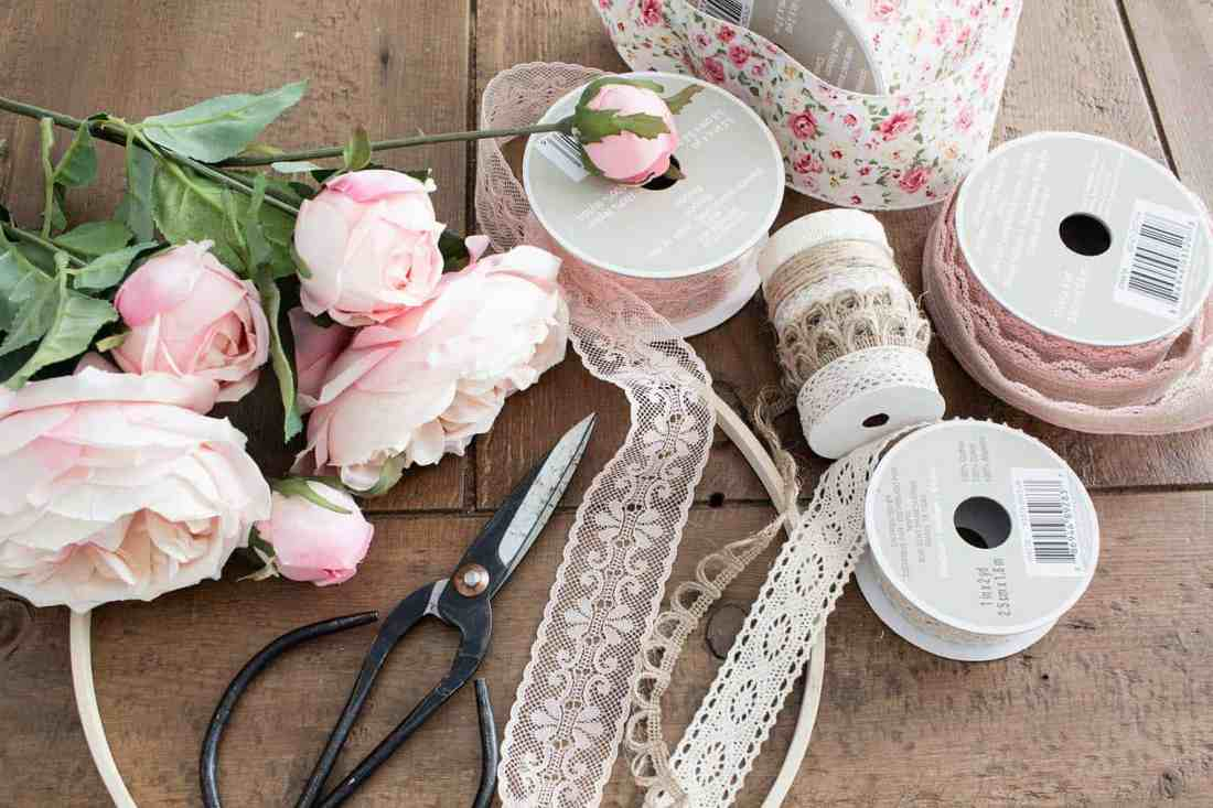 Floral boho spring hoop wreath supplies: ribbon, faux flowers, scissors, glue gun, embroidery hoop and a scrap piece of cardboard.