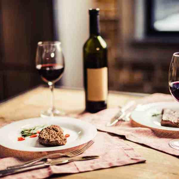 wine bottles on table, steak dinner