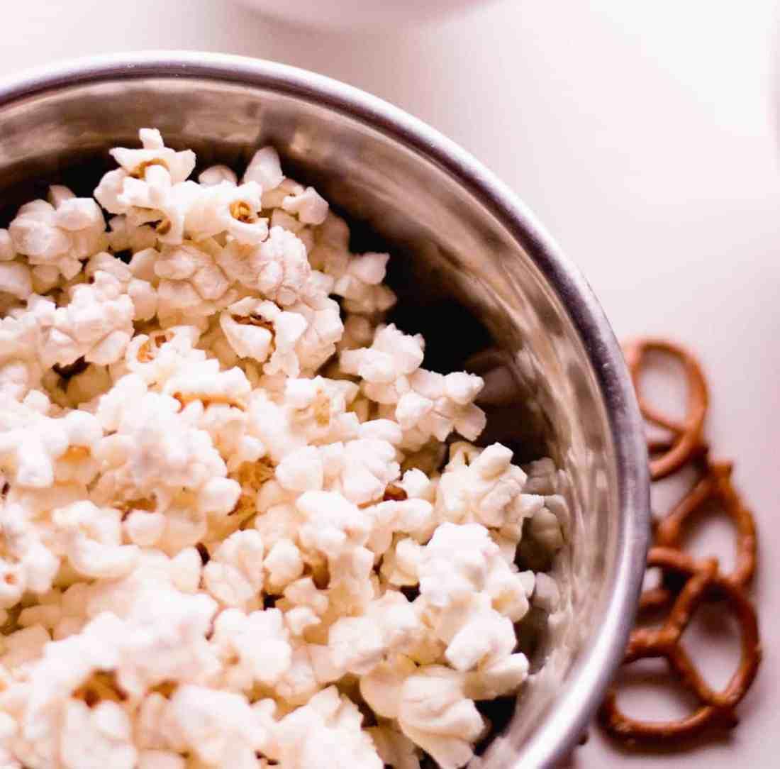 popcorn in metal bowl, pretzels on counter