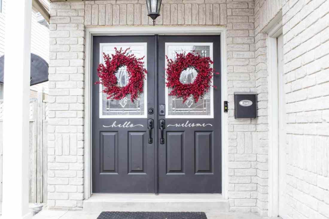 black double front doors with black door hardware and red berry wreaths