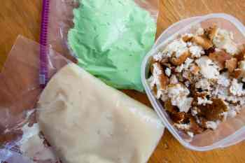 layering ingredients for trifle: cream cheese mixture, green icing and broken up cakes pieces