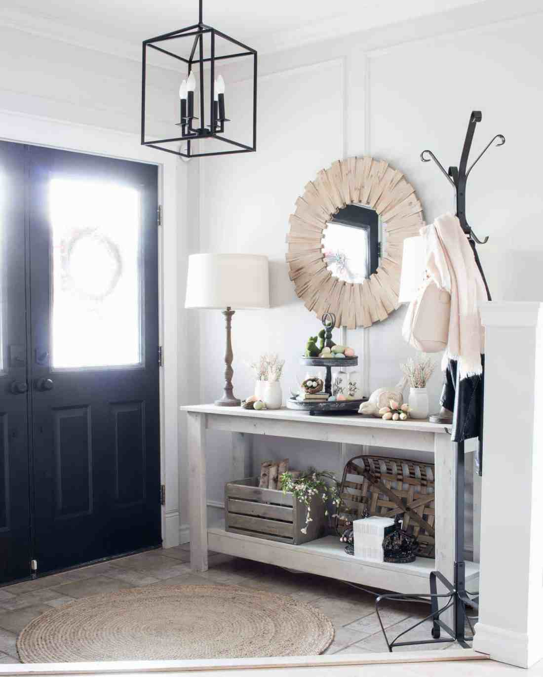 black doors with neutral and blush pink spring decor in entry