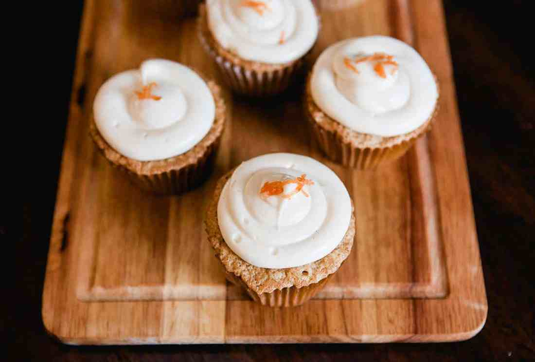 carrot cupcakes with cream cheese icing from above, on a cutting board